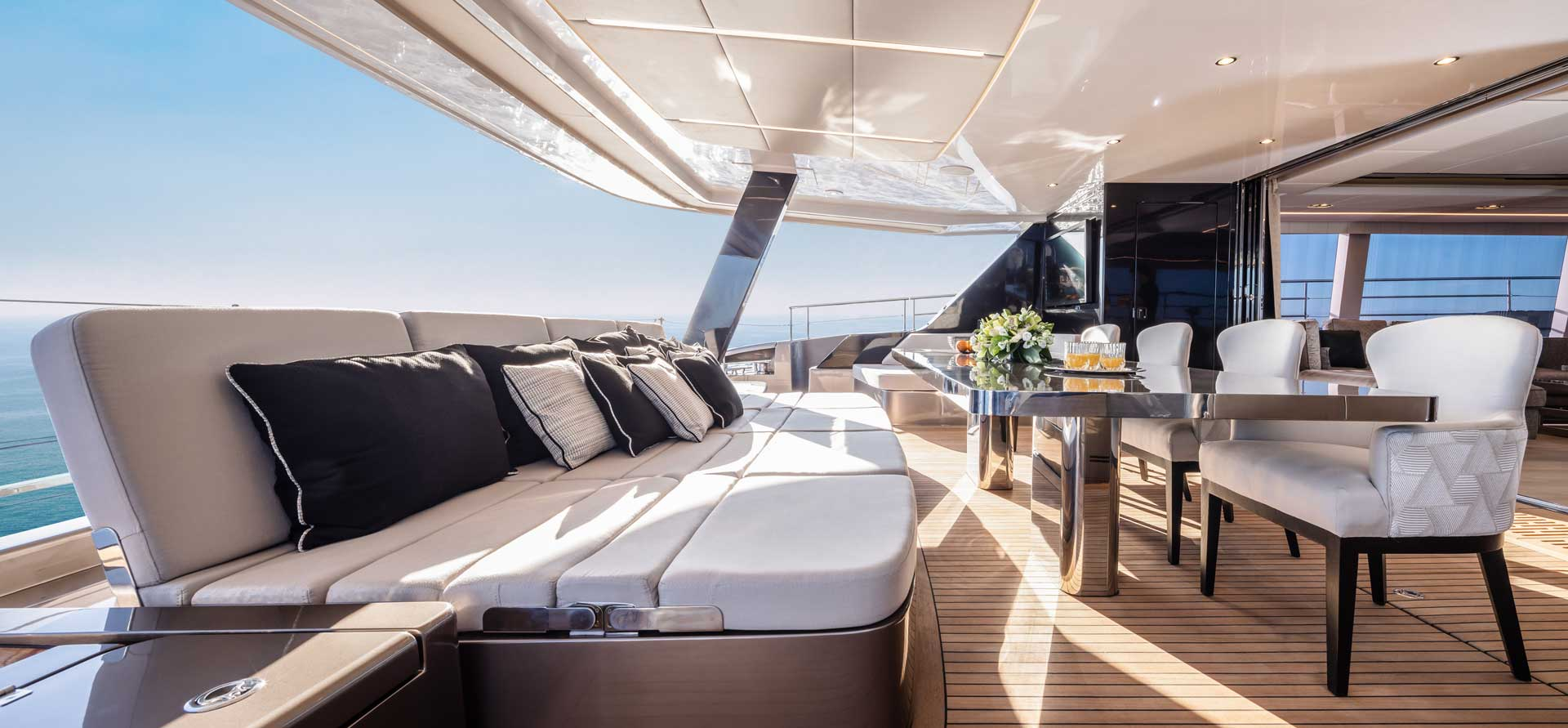 Ample aft cockpit of the 80 Sunreef Power Eco with the outdoor relaxation area with seating along with a wet bar.