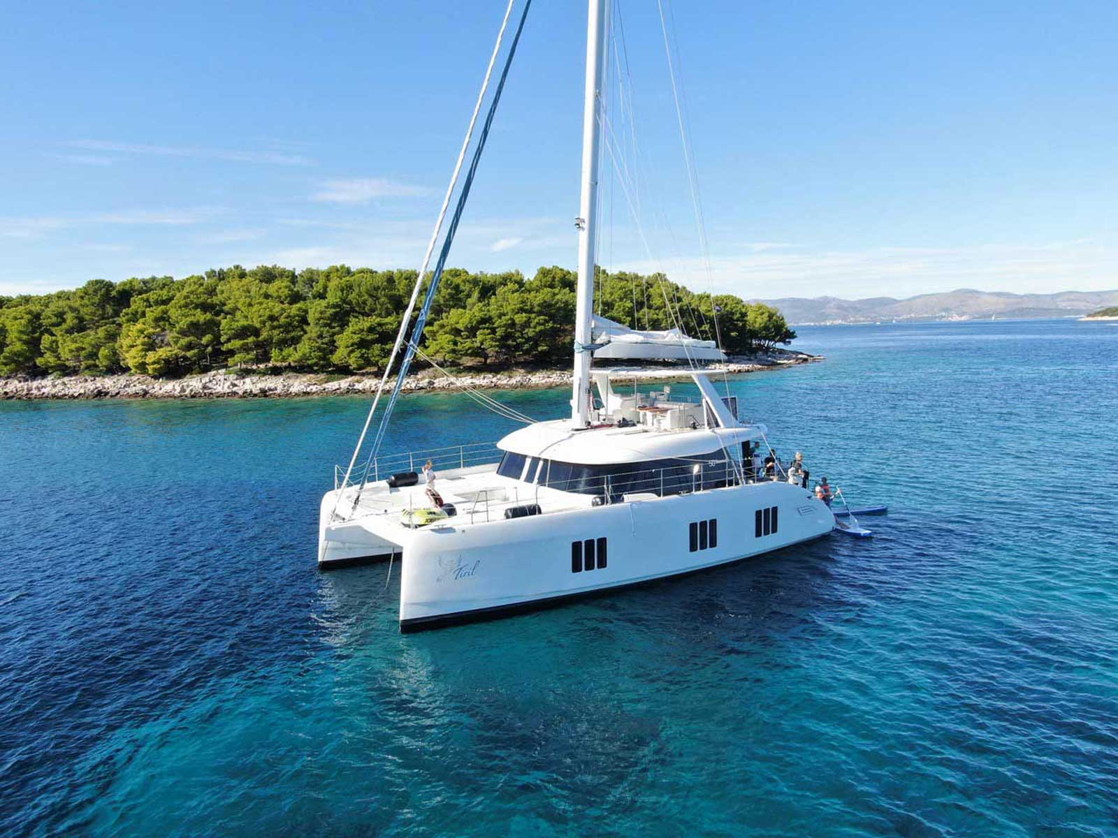 The electric sailing catamaran Sunreef 50 Eco at anchor in the lagoon nearby a small island.