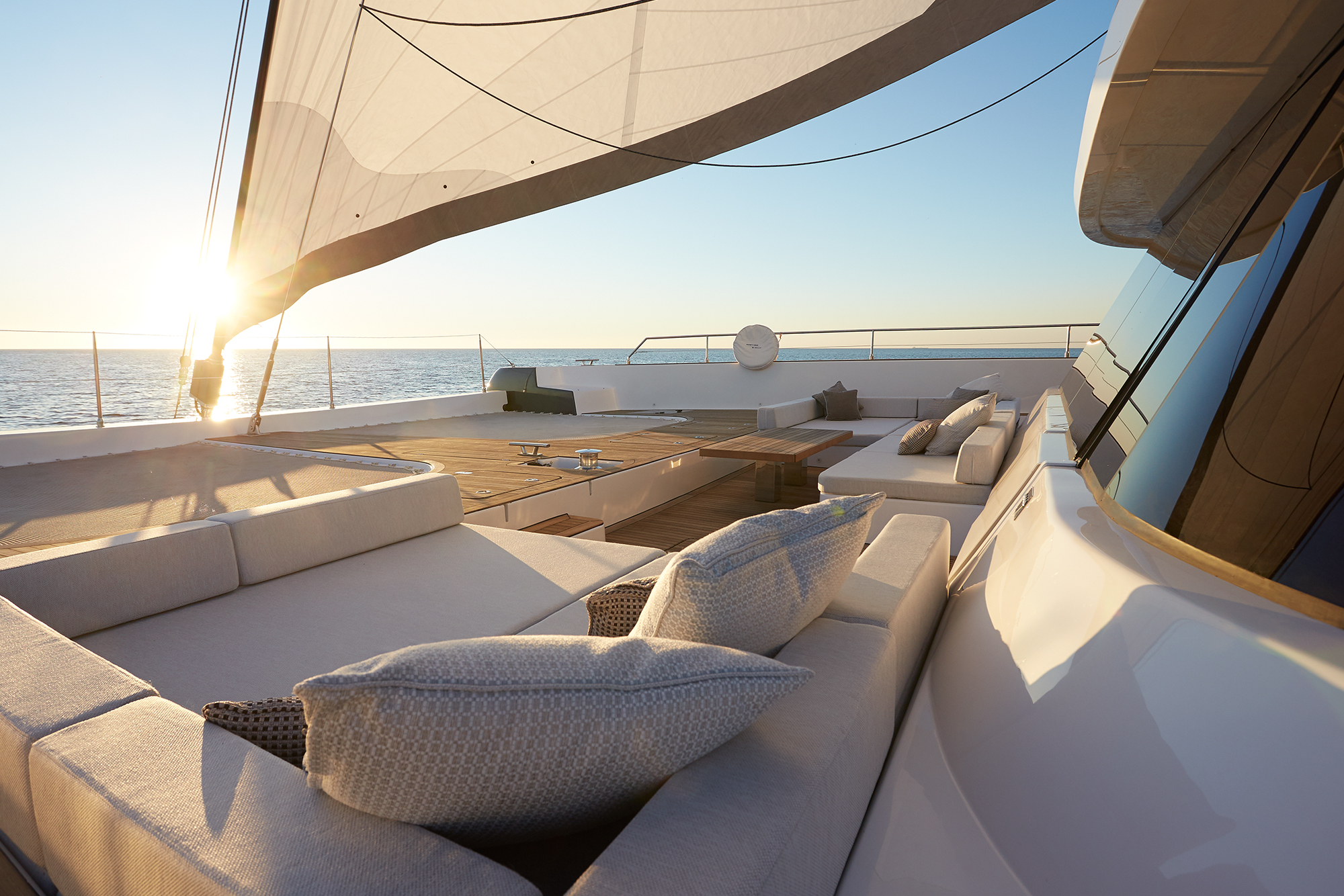 Lounging space on the bow terrace with two beige sofas on both sides on the electric sailing catamaran Sunreef 80 Eco.